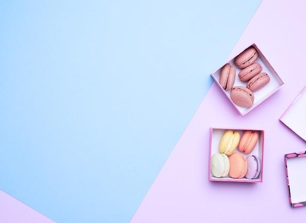 Macarons ronds multicolores cuits dans des boîtes carrées