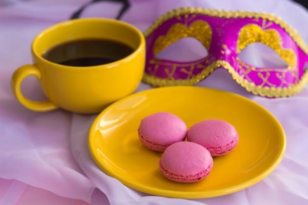 Macarons roses sur une assiette jaune, une tasse de café jaune et un masque rose