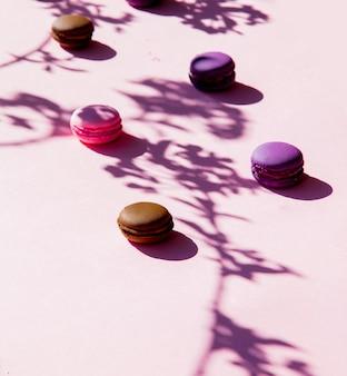 Macarons roses et ombre de branche sur une surface rose. vue ci-dessus
