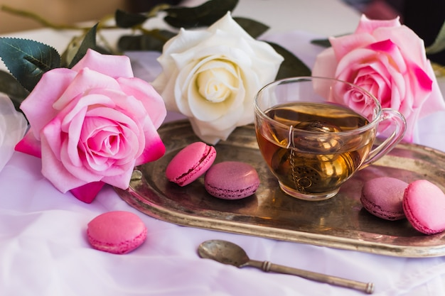Macarons roses, thé chaud sur un plateau vintage argenté flou fond de roses
