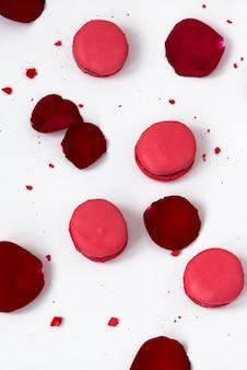 Macarons rouges aux pétales de rose sur un tableau blanc.