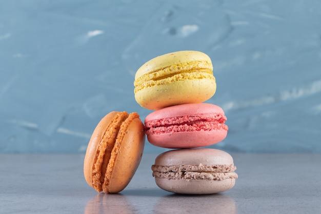 Macarons sucrés colorés crémeux placés sur une surface en marbre