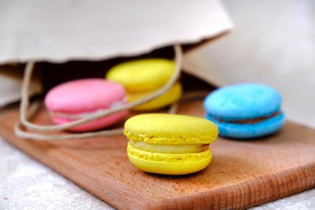 Macarons sucrés français colorés de sac en papier sur une plaque en bois.