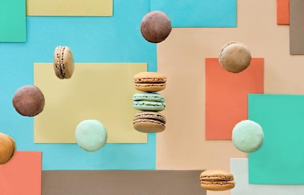 Macarons sucrés et savoureux, à plat sur une table en papier géométrique