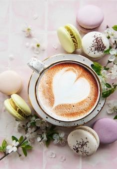 Macarons avec une tasse de café et une branche de fleurs blanches sur une surface de carrelage rose