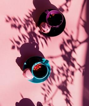 Macarons et tasse de thé avec des ombres sur la surface rose
