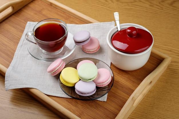 Macarons et une tasse de thé sur un plateau en bois