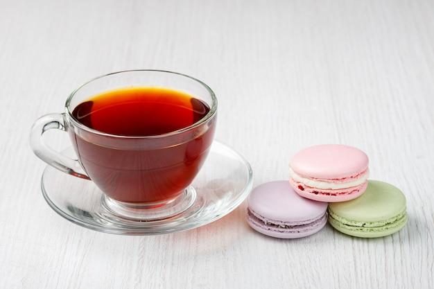 Macarons et une tasse de thé sur une table en bois clair