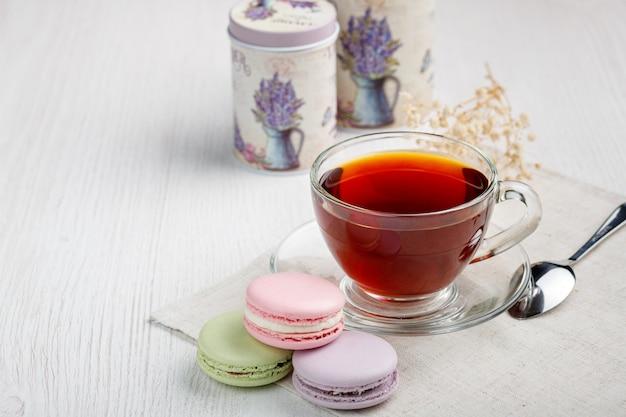 Macarons et une tasse de thé sur une table de cuisine en bois clair