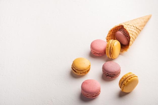 Macarons versés hors de cône de pâtisserie sur l'espace de vue de dessus de surface blanche