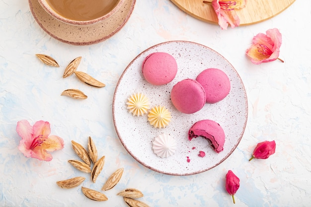 Macarons violets ou gâteaux macarons avec tasse de café sur un fond de béton blanc décoré de fleurs. vue de dessus, mise à plat,