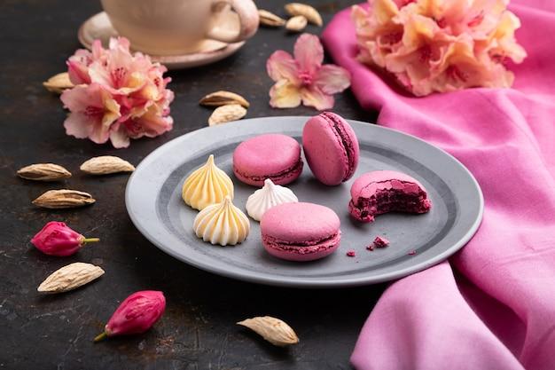 Macarons violets ou gâteaux macarons avec tasse de café sur fond de béton noir et textile rose. vue de côté,