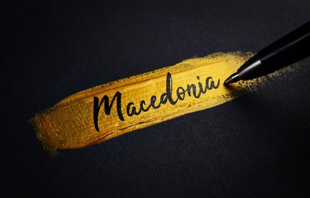 Macédoine texte d'écriture sur le coup de pinceau de peinture dorée
