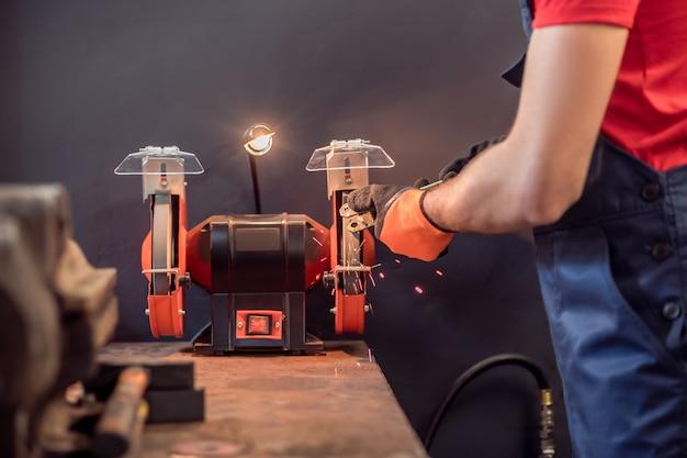 Machine à affûter. main expérimentée du travailleur en salopette avec détail près de la meule rotative éclairée en atelier