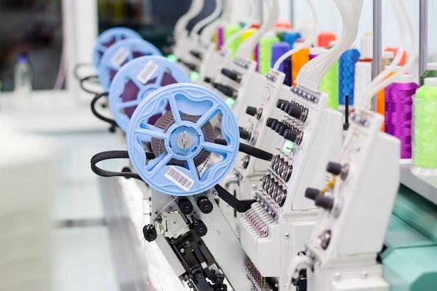 Machine à broder moderne avec un dispositif pour coudre des paillettes et des fils colorés.