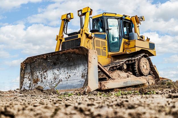 La machine de bulldozer nivelle le chantier de construction. le génie civil avec la chenille déplace la terre. fermer. machinerie lourde de construction.