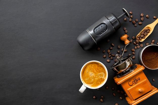 Machine à café expresso, tasse et haricot sur table en bois noir. vue de dessus