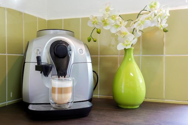 Machine à café avec un latte macchiato dans une maison décorative confortable avec mur végétal et fleurs. café fait maison