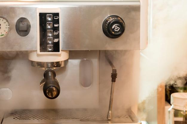 Machine à café professionnelle avec de la fumée sur le café.