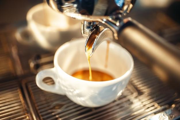Machine à café verse de la mousse dans la tasse gros plan