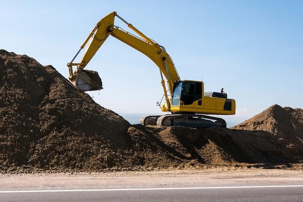 Machine de chargeur d'excavatrice jaune pendant les travaux de terrassement sur ciel bleu. levage de chargement de machines de construction sur les chantiers