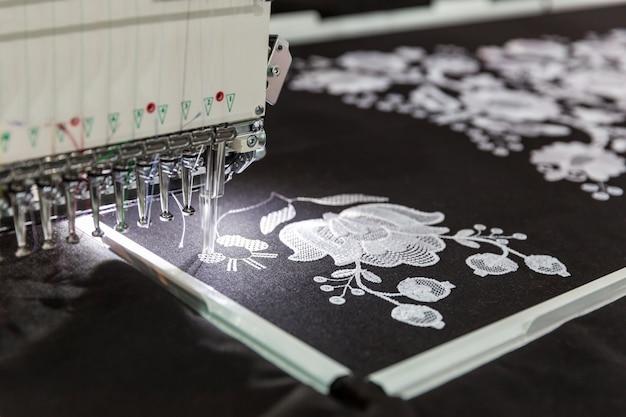 Machine à coudre au travail, tissu textile, personne