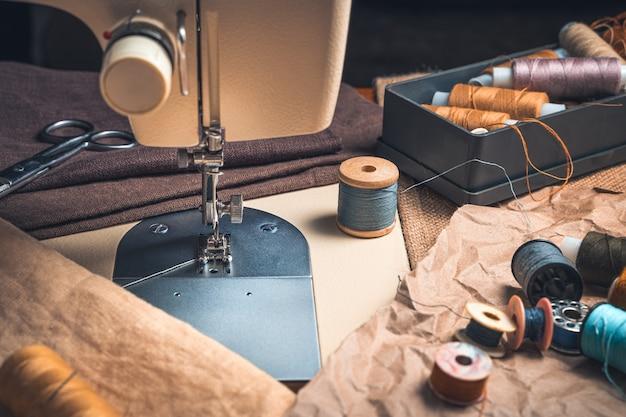 Une machine à coudre en gros plan et un ensemble de fils. vue de côté, finition vintage.