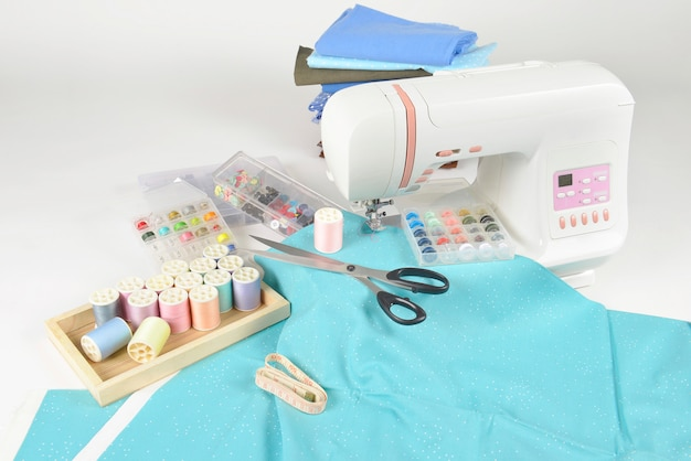 Machine à coudre et rouleaux de fils colorés, ciseaux, tissus et accessoires pour la couture.