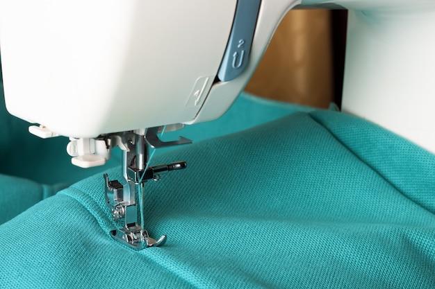 Machine à coudre avec tissu turquoise et fil, gros plan