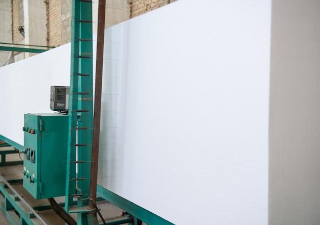 La machine coupe le plastique mousse. usine de production de panneaux sandwich en polystyrène
