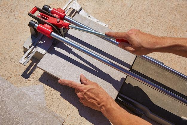 Machine à couper les carreaux avec des mains de maçon