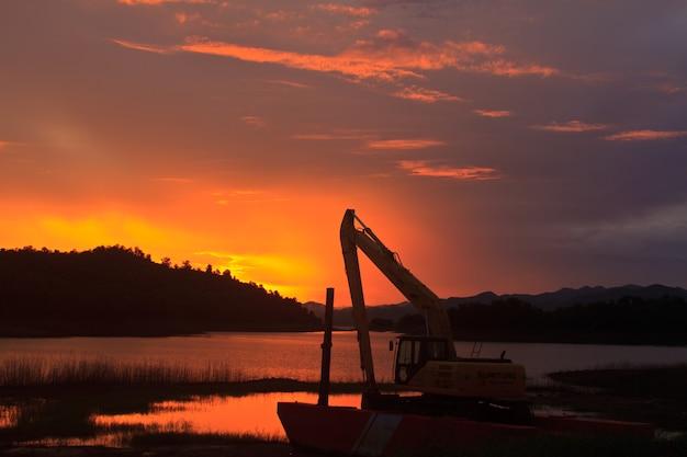 Machine dans le chantier près du lac au coucher du soleil