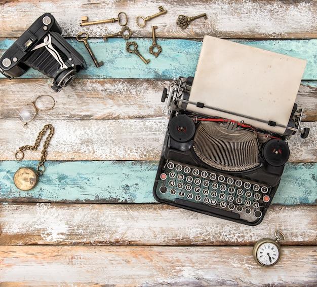 Machine à écrire antique et accessoires vintage sur table en bois. mise à plat nature morte
