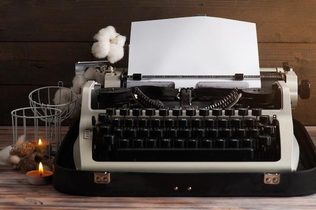 Machine à écrire bouchent et fleurs séchées avec bougie aromatique allumée. papier vintage tonique et kraft