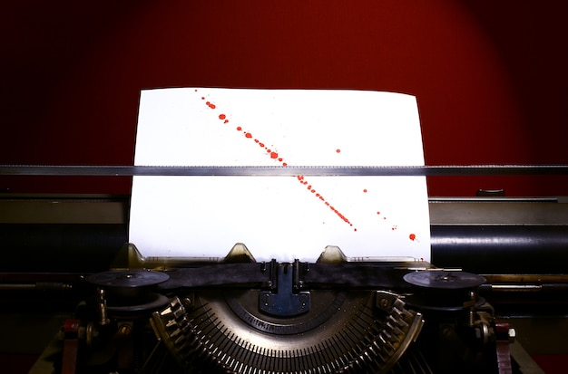 Machine à écrire avec des éclaboussures de sang sur fond de papier.