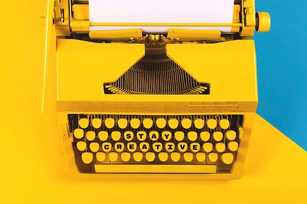 Machine à écrire jaune vif comme symbole d'écriture, de nouvelles idées, de créativité et de narration