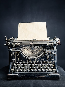 Machine à écrire noire vintage avec feuille de papier insérée