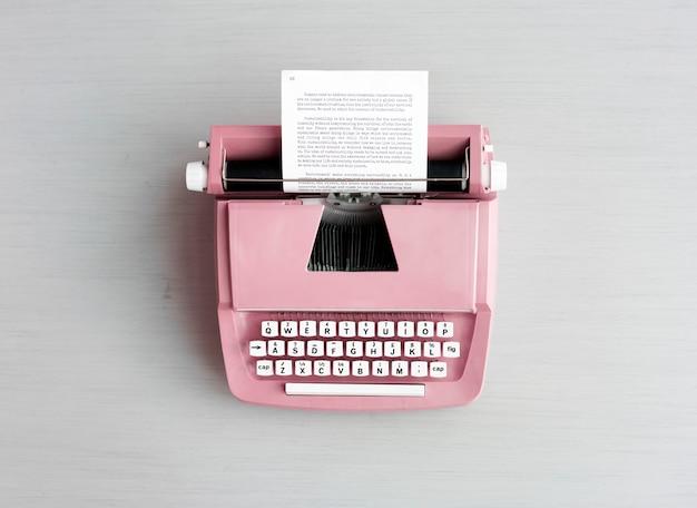 Machine à écrire pastel rétro sur surface grise