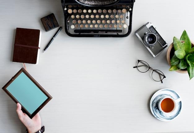 Machine à écrire rétro avec une main tenant un cadre photo en bois sur une table grise