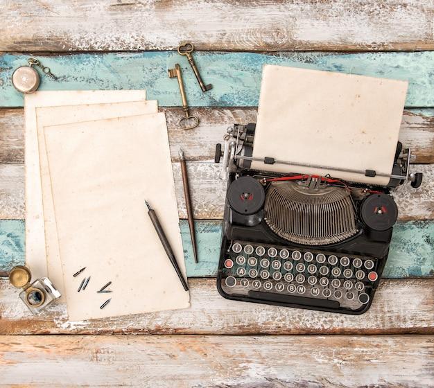 Machine à écrire vintage et feuilles de papier usagées sur table en bois. mise à plat nature morte