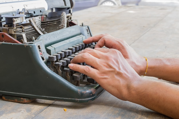 Machine à écrire vintage et main de l'homme sur une table en bois