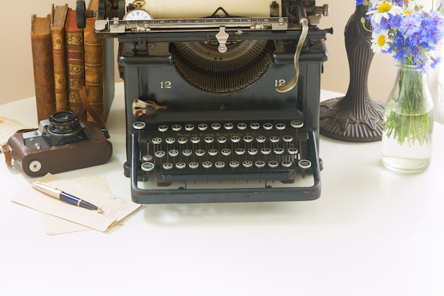 Machine à écrire vintage noire avec des livres sur une table en bois blanche