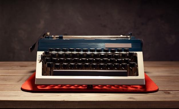 Machine à écrire vintage à table en bois près de la surface d'arrière-plan du mur, concept de scénariste ou d'écrivain rétro