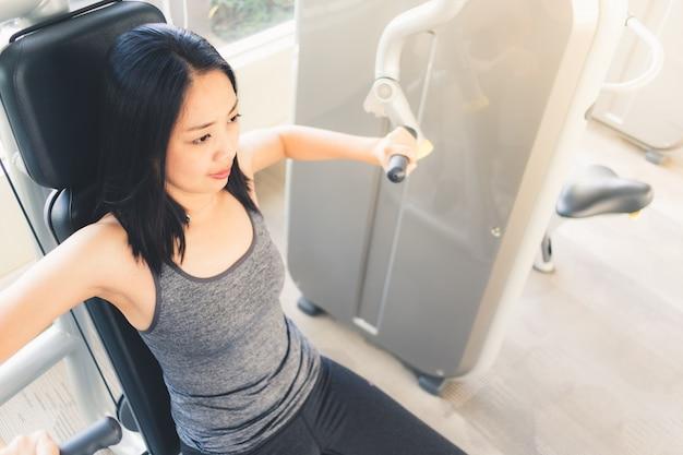 Machine d'entraînement de câble de presse banc femme dans la salle de fitness.