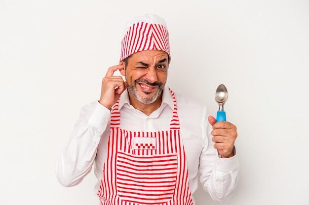 Machine à glaçons caucasienne d'âge moyen homme de race blanche tenant une cuillère isolée sur fond blanc couvrant les oreilles avec les mains.