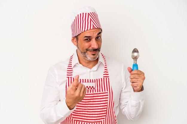 Machine à glaçons caucasienne d'âge moyen homme de race blanche tenant une cuillère isolée sur fond blanc pointant du doigt vers vous comme s'il vous invitait à vous rapprocher.