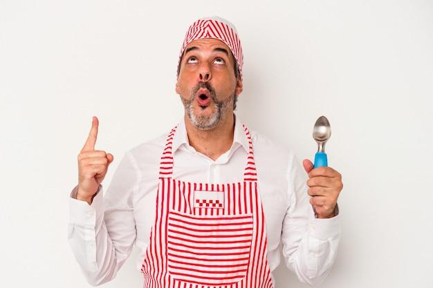 Machine à glaçons caucasienne d'âge moyen homme de race blanche tenant une cuillère isolée sur fond blanc pointant vers le haut avec la bouche ouverte.