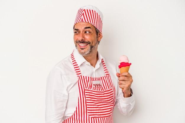 Machine à glaçons caucasienne d'âge moyen homme de race blanche tenant une glace isolée sur fond blanc regarde de côté souriant, gai et agréable.
