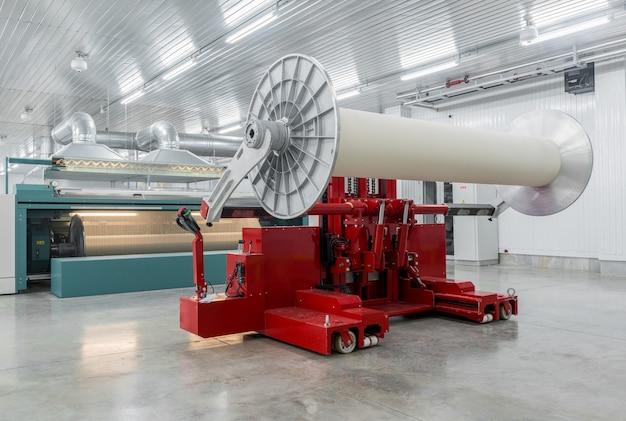 La machine hydraulique de levage soulève de grandes bobines. filature et filature