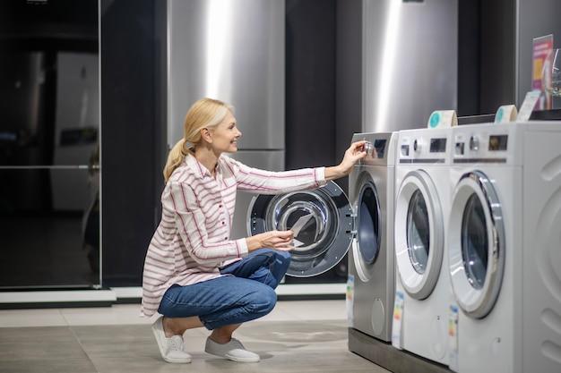 Machine à laver. clientèle féminine en chemise rayée en choisissant une machine à laver dans le mégastore